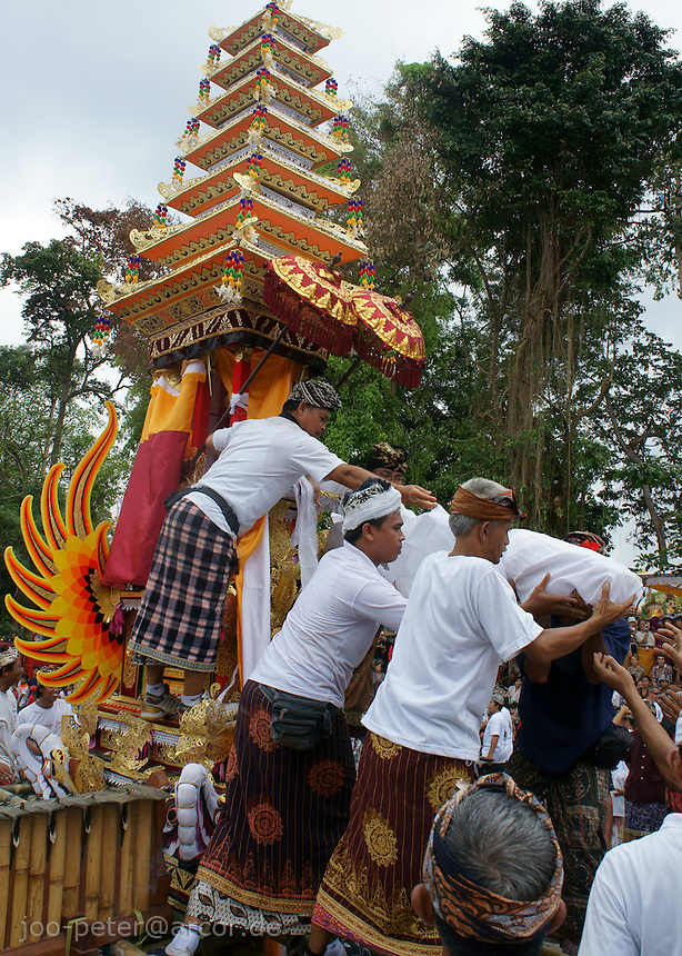 reminders of the passed family member, wrapped in white cotton,  are carfully taken of the  tower-like shaped carriage,   to be placed in the sculpture of a black bull, to be burned with offerings  in  cremation ceremonies, guiding the spirit of the death from underworld to heavenly realms,  17.9.2011,  family Budiana,  Banjar Pande, Peliatan, Bali, Indonesia