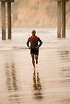 Hispanic man jogging on beach