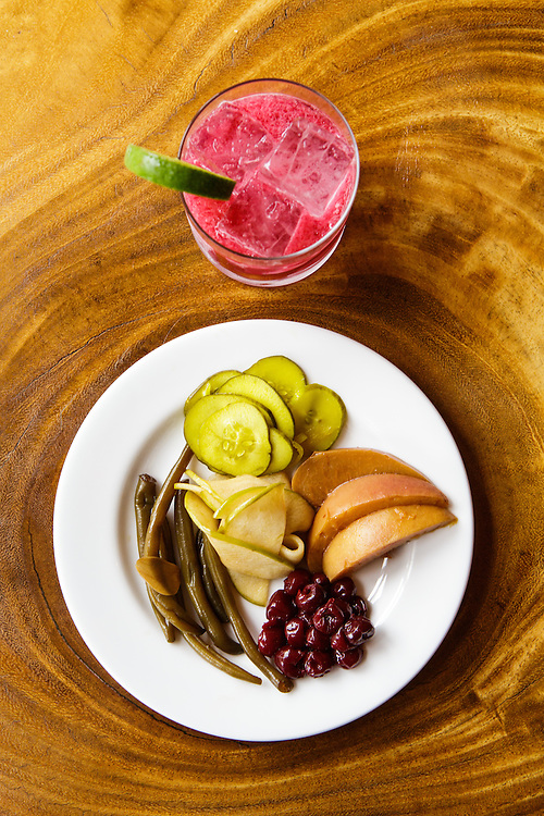 Durham, North Carolina - Monday September 28, 2015 - The Pickle Plate at Alley Twenty Six is an evolving, seasonal plate created by Jonathan Merz. It is seen here featuring ponzu mirin green beans with sliced garlic, dark spiced cherries, miso white soy peaches from Lyon Farms, bread and butter cucumbers and granny smith apple slices with habeñero, cilantro and chili spices. It is paired here with a drink called the Mexican Herbalist which is currently on the menu.
