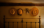 Three straw hats hanging above an old bed frame