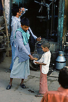 Indian boy buying snack food from street seller, India