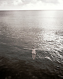 HONDURAS, Roatan, woman floating on sea surface (B&W)