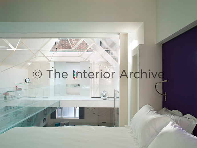 A view across the atrium through the glass wall of the bedroom to the bathroom