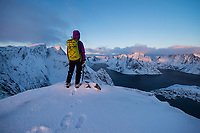 Female hiker takes in winter view over fjord from Reinebringen, Moskenesøy, Lofoten Islands, Norway