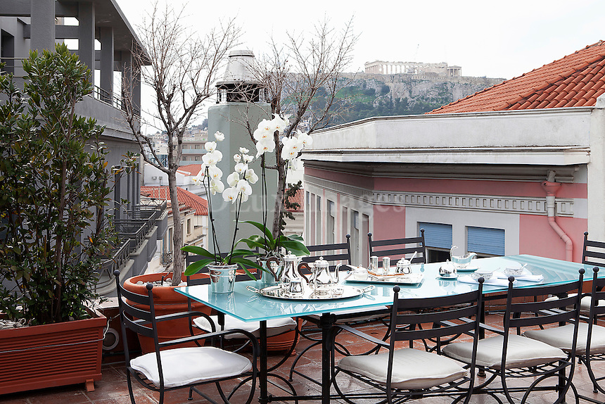 balcony glass table<br /> <br /> Interior architect George Efthimiou designed his maisonette apartment in downtown Athens, Greece. It&rsquo;s a renovated 125 square meter art deco loft, first built in 1935 with a view of the Acropolis.