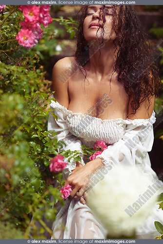 Sensual glamour portrait of a beautiful sexy young woman with wet hair sitting in the rain in a rose garden