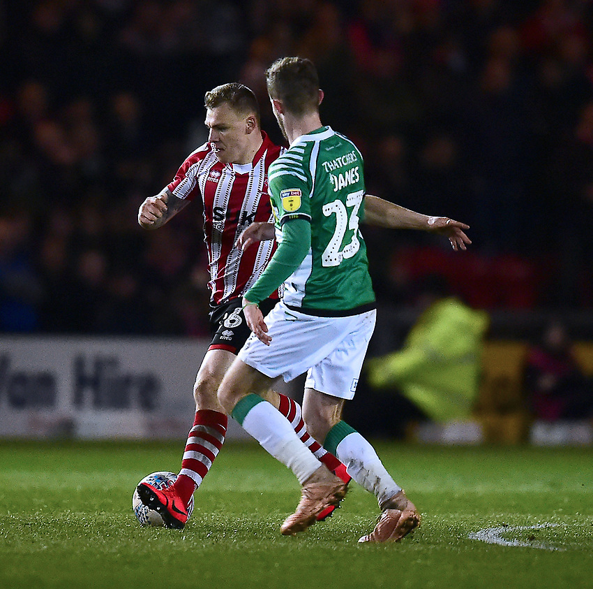 Lincoln City's Harry Anderson under pressure from Yeovil Town's Tom James<br /> <br /> Photographer Andrew Vaughan/CameraSport<br /> <br /> The EFL Sky Bet League Two - Lincoln City v Yeovil Town - Friday 8th March 2019 - Sincil Bank - Lincoln<br /> <br /> World Copyright © 2019 CameraSport. All rights reserved. 43 Linden Ave. Countesthorpe. Leicester. England. LE8 5PG - Tel: +44 (0) 116 277 4147 - admin@camerasport.com - www.camerasport.com