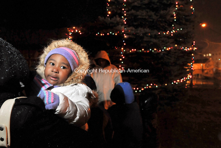 WATERBURY, CT-05 DECEMBER 2009-120509JS02-Desire Salley, 2, of Waterbury, being held by her bother Natasha Salley as guests sing songs during the Christmas tree lighting Saturday at Martin Luther King, Jr., Memorial Park in Waterbury. The event was sponsored by the Greater Waterbury NAACP and Faith Generation Ministries. <br /> Jim Shannon Republican-American