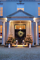 The portico of this Grade I listed 17th century manor house is decorated with a wreath and a pair of illuminated Christmas trees