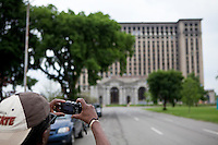 A man takes a photo of the vacated Michigan Central Station in the Corktown district of Detroit  Sunday June 9, 2013. Built for the Michigan Central Railroad, Michigan Central Station (also known as Michigan Central Depot or MCS) was Detroit's passenger rail depot from its opening in 1913  until the cessation of Amtrak service on January 6, 1988.