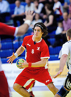 11 JUN 2010 - LONDON, GBR - Martin Hare (Great Britain - red) looks for a way through the Estonian defence (white and black) during the two teams 2012 European Handball Championships Qualification Tournament match (PHOTO (C) NIGEL FARROW)