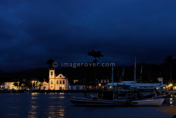 Nighfall over the harbour and Paraty's oldest church, the Nossa Senhora dos Pardos Libertos (built 1722); Paraty, Espirito Santo, Brazil. The beautiful colonial town of Paraty has been a UNESCO World Heritage Site since 1958. --- No signed releases available.