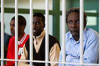 Da sinistra, Mohamed Isse Karshe, Abdi Hassan Mahamur ed Ahmed Malimed Ali, presunti pirati somali accusati dell'attacco alla nave portacontainer italiana Montecristo, durante la prima udienza del processo presso la III Corte d'Assise a Roma, 23 marzo 2012. La nave, assaltata il 10 ottobre 2011 al largo della Somalia, venne liberata il 15 ottobre dai Royal Marines britannici con l'ausilio di una nave militare statunitense..Somali allegedly pirates, from left, Mohamed Isse Karshe, Abdi Hassan Mahamur and Ahmed Malimed Ali sit inside a cage during the opening audience for the assault to the Montecristo container ship, in Rome, 23 march 2012. The ship was attacked on 10 october 2011 and freed by US navy and British Royal Marines on 15 october..UPDATE IMAGES PRESS/Riccardo De Luca