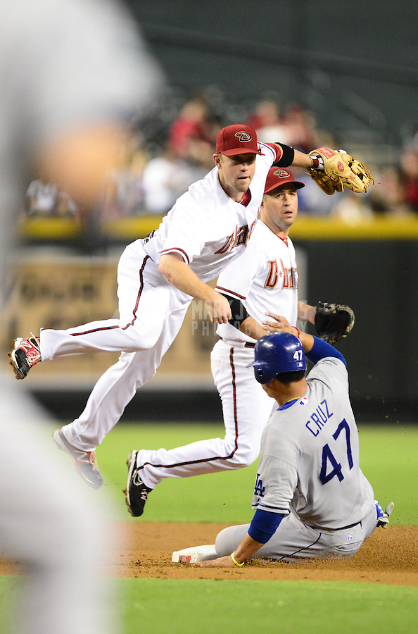 Sept. 11, 2012; Phoenix, AZ, USA: Arizona Diamondbacks second baseman Aaron Hill leaps in the air after throwing to first base to complete the double play after forcing out Los Angeles Dodgers base runner Luis Cruz in the second inning at Chase Field. Mandatory Credit: Mark J. Rebilas-