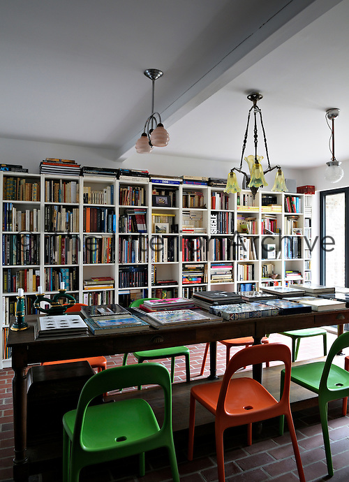 Plastic chairs in alternating lime green and orange flank a refectory table in the library