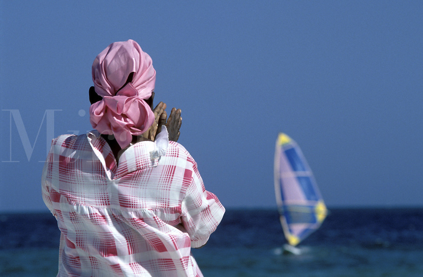 Kenyan woman on beach looking at windsurfer out at sea