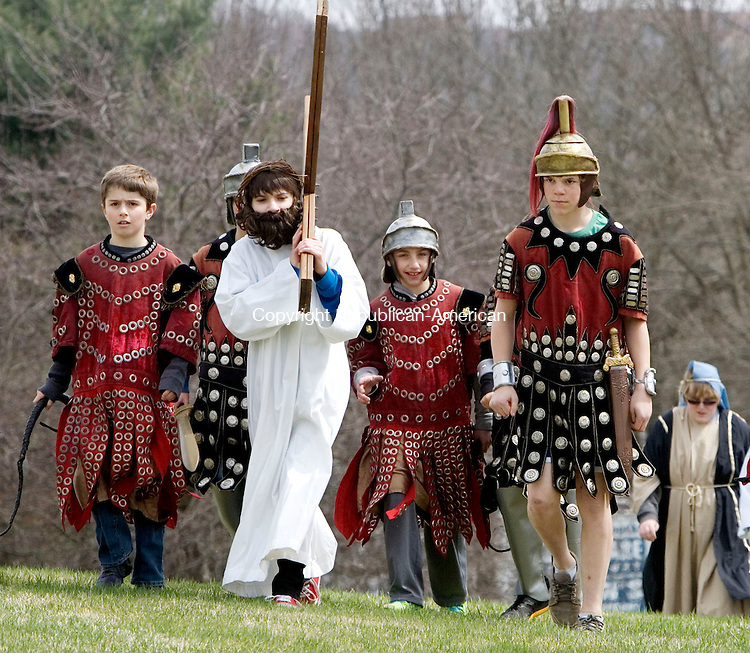SOUTHBURY CT. 18 April 2014-041817SV09-Peter Dzubay, 14, of Southbury carries the cross while playing Jesus during the Good Friday Faith Walk at Sacred Heart Church in Southbury Friday. <br /> Steven Valenti Republican-American
