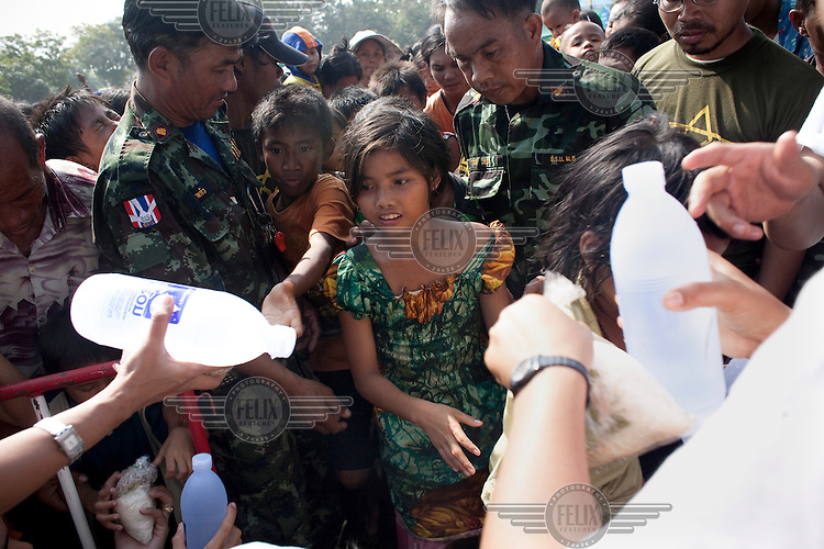 A young Karen girl collects water and food at the refugee centre in Mae Sot. An estimated 20,000 Burmese refugees fled into Thailand to escape clashes in the border towns of Myawaddy and Pyaduangsu, only a day after a Burmese election which critics described as a sham..Ethnic minorities along the Thai-Burma border had warned earlier that the junta would launch a major offensive after the election, as many armed rebel groups had refused to become part of the government-controlled Border Guard Forces.