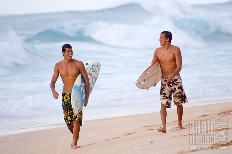 Two young men having a conversation while walking on the beach returning from a surf session.