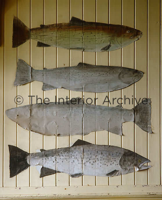 A series of paper cutouts of salmon is used to decorate the clapboard walls of the fishing lodge