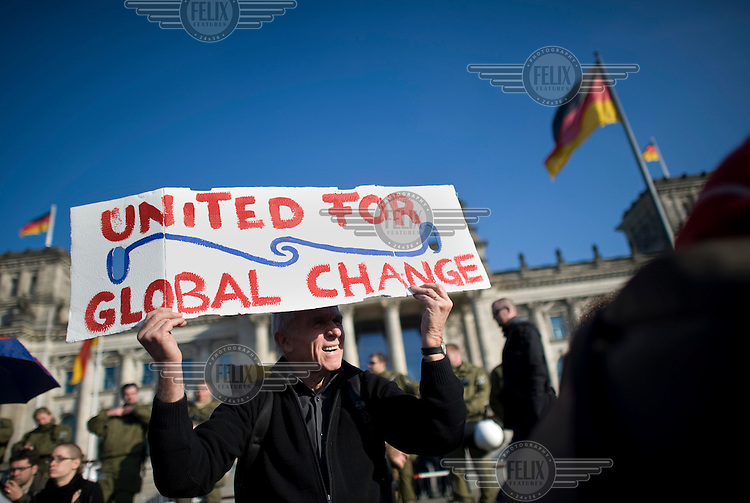 A protestor, outside the Reichstag, holds up a placard that reads: United for Global Change, during a march linked to the Occupy Movement a worldwide protest against the banking industry and the prevailing economic system.