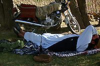 A foot soldiers from the Wardak Mobile Patrol Unit takes a rest/nap by his chinese motorcycle armed with AK47 Kalashnikov