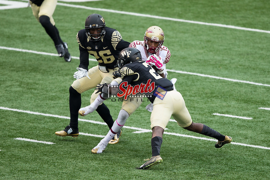 Travis Rudolph (15) of the Florida State Seminoles is tackled by Cameron Glenn (2) and Thomas Brown (26) during second half action at BB&T Field on October 3, 2015 in Winston-Salem, North Carolina.  The Seminoles defeated the Demon Deacons 24-16.   (Brian Westerholt/Sports On Film)