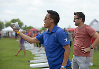 NWA Democrat-Gazette/BEN GOFF @NWABENGOFF<br /> Vincent Tran (left) takes his throw as teammate Todd Jackson, both with Advanced Solutions, waits his turn Friday, June 16, 2017, during the Catfish, Corndogs and Cornhole tournament at Mercy Hospital in Rogers. The event is an annual fundraiser hosted by WhyteSpyder, with proceeds from this year's tournament benefiting Mercy Health Foundation. Some 140 teams of two entered this year, according to WhyteSpyder CEO Eric Howerton.