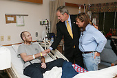 Bethesda, MD - December 19, 2007 -- United States President George W. Bush visits United States Navy Hospital Corpsman Christopher Braley and his mother, Debra Braley, of Manteca, California, at the National Naval Medical Center in Bethesda, Maryland, Wednesday, December 19, 2007. Braley is recovering from injuries sustained in Operation Iraqi Freedom. .Credit: Joyce N Boghosian - White House via CNP