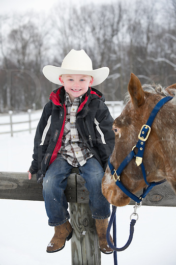 Young boy sitting on fence enjoying himself with Appaloosa horse, missing tooth, cute five year old dressed in white cowboy hat, winter snow scene in Pennsylvania, PA, USA.