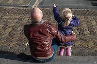 Nederland, Utrecht, 4 febr 2014<br /> Vader zit met zijn dochtertje op een stoeprandje om wat te drinken.<br /> Foto: Michiel Wijnbergh