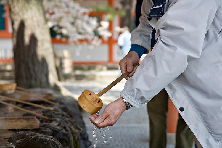 "Man washing hand, called ""temizu,"" at Heian-Jingu Shrine in Kyoto Japan"