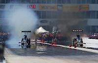 Apr. 28, 2013; Baytown, TX, USA: NHRA top fuel dragster driver J.R. Todd (left) smokes the tires racing alongside Khalid Albalooshi during the Spring Nationals at Royal Purple Raceway. Mandatory Credit: Mark J. Rebilas-