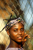 Ujiji, Tanzania. Smiling woman with braids and cloth headband beside a chan link fence.