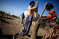 two women crush grain in front of their hut in Lafaissa, Somali Region, Ethiopia on Monday November 9 2009. .The Lafaissa school is supported by the British non governmental organization Save the Children UK..
