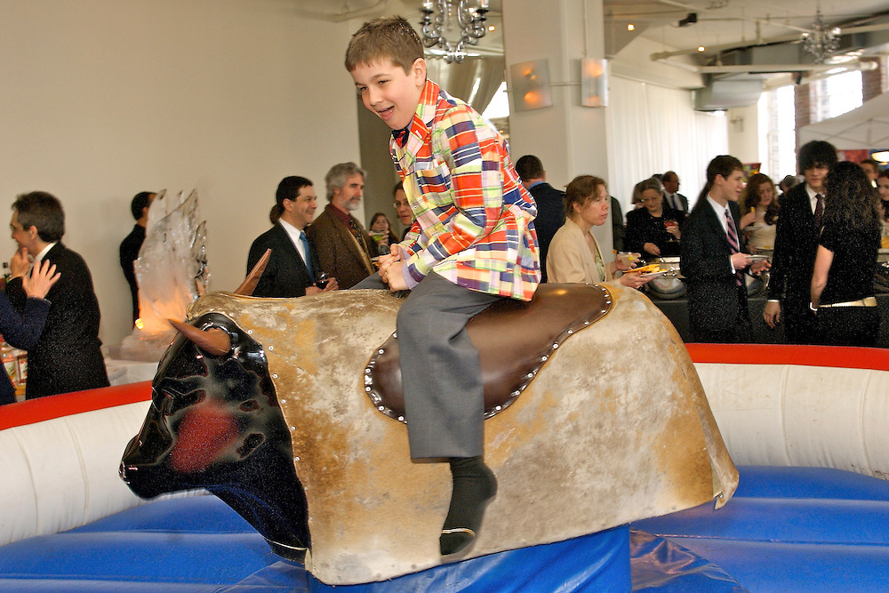Boy riding a mechanical bull at a rodeo themed Mitzvah at Tribeca Rooftop in NYC.