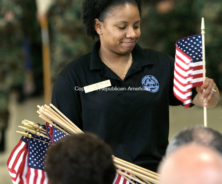 WATERBURY, CT--15 JUNE 2006 -061506JS04- Tamara Jex, a member of the Connecticut National Gurad Office of Family Programs, hands out American flags prior to the send off ceremony for members of the Connecticut National Guard's 143rd Combat Sustainment Support Battalion Thursday at the Waterbury Armory. 70 members of the group will be deployed to Iraq for 18 months following training at Fort Dix in New Jersey. -- Jim Shannon Republican-American