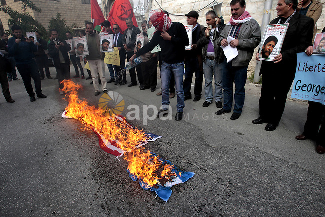 Palestinian protesters burn French flag and israeli, during a protest outside the French Cultural Center calling for the release of Lebanese militant Georges Ibrahim Abdallah and Ahmed Saadat, leader PFLP, in the West Bank City of Nablus on January 23, 2013. Photo by Nedal Eshtayah