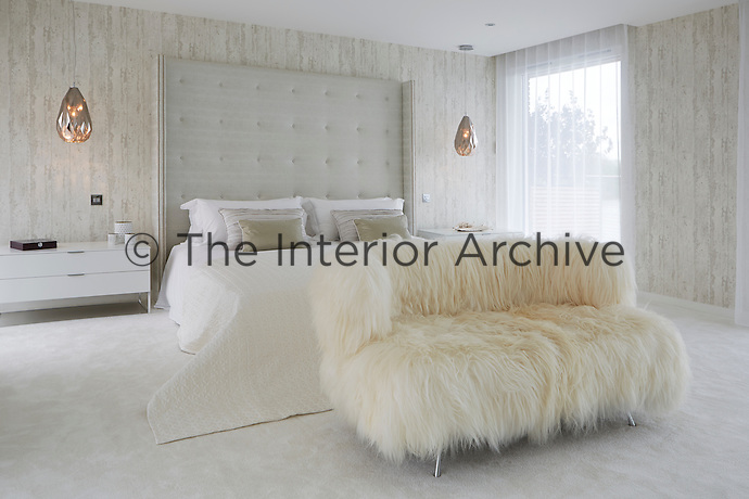 The master suite is a calm and tranquil space in off whites and neutrals. A winged headboard has been added to the super-king size bed, in a silver embossed faux animal skin fabric to gently frame the room, studded on the leading edges with rows of small chrome studs for definition. Texture was added with quirky Icelandic sheep clad fur sofa and the walls are finished in softly textured vinyl wallpaper with hints of distressed wood cladding. As walls of glass flank both sides of the bedroom, full length white sheers were made to filter sunlight and add a calming elegance to the space. Warmth was added by faceted copper glass pendant chandelier lights. The sheers running in clean pocket headers either side of the master bedroom soften the edges.