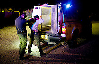 A Borer Patrol agent searches an illegal migrant after being spoted by a citizen and reported to officials near Green Valley, Arizona, August 9, 2009. In addition to traffic stops and drug busts, the sheriff department is primarily responsible for responding to dead body calls and body recovery and transfer from the desert to the medical examiners office in Tucson...PHOTOS/ MATT NAGER