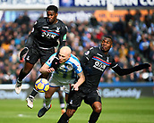 17th March 2018, The John Smiths Stadium, Huddersfield, England; EPL Premier League football, Huddersfield Town versus Crystal Palace; Jeffrey Schlupp of Crystal Palace wins a challenge with Aaron Mooy of Huddersfield Town with Christian Benteke of Crystal Palace close by