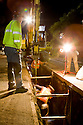 """Night construction crew works on installing 24"""" diameter pipes made of recycled steel in a trench as part of a reclaimed water pipeline. The pipes are first covered with purple plastic sleeves to prevent corrosion and to identify them as carrying reclaimed water. The cities of Palo Alto and Mountain View are jointly constructing a reclaimed water pipeline to carry recycled water from the Palo Alto Regional Water Quality Control Plant to customers along East Bayshore Parkway and Mountain View's North Bayshore area."""