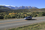 Silver sedan with Sneffels Range behind, in the San Juan Mountains, autumn, Colorado.