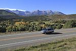 Silver sedan with Sneffels Range behind, in the San Juan Mountains, autumn, Colorado.