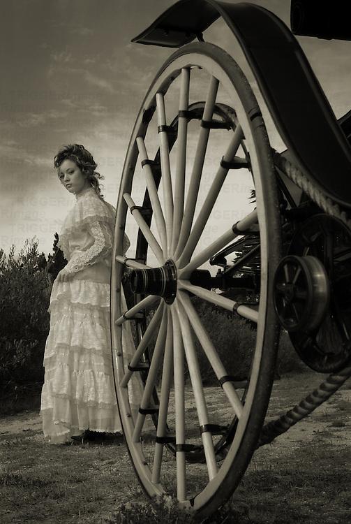 A model wearing a victorian dress near a cart wheel
