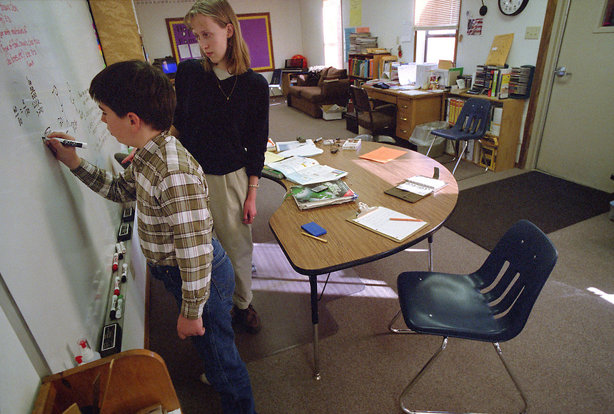 Joe Kennedy, 13, the lone student at Cozy Hollow Elementary School on the Kennedy ranch in Wyoming, works a math problem for teacher Rebecca Rodgers, 23. Wyoming, one of the nation's most rural states, supports many isolated schools with few students. (Kevin Moloney for the New York Times)