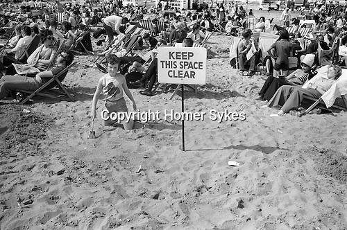 Blackpool Beach Lancashire Uk. 1970s. Holidaymakers sun themselves crowded beach. Keep this Space Clear. A safty warning...