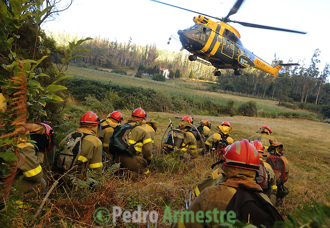 Members of the fire Galician brigade are seen around the area where a fire burns in Porqueira, near A Coruña, on august 14, 2010, near Ourense.  Pedro ARMESTRE