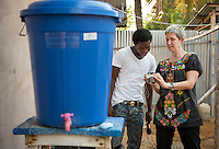Occidental College professor Mary Beth Heffernan shows health care worker Altu Burnette his photo at ELWA II ETU (Ebola treatment unit) in Monrovia, Liberia on Sunday, March 1, 2015. The photos will be used in Professor Heffernan's PPE Portrait Project. A large container filled with a bleach-water mixture used by all staff to wash their hands (mandatory) is in the foreground.<br /> (Photo by Marc Campos, Occidental College Photographer) Mary Beth Heffernan, professor of art and art history at Occidental College, works in Monrovia the capital of Liberia, Africa in 2015. Professor Heffernan was there to work on her PPE (personal protective equipment) Portrait Project, which helps health care workers and patients fighting the Ebola virus disease in West Africa.<br />