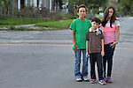 Rosaura Pineda and her children Isaac and Celeste stand in a street in San Antonio, Texas, on December 3, 2015. Pineda and her children fled Honduras in 2015 because of domestic violence and pressure on her children from gangs. After requesting political asylum in the United States, she was held for several days by immigration officials and then released with an ankle monitor, which she is fighting to have removed as she claims it makes her feel like a criminal. She and her children are staying in a shelter in San Antonio run by the Refugee and Immigrant Center for Education and Legal Services (RAICES) and supported by a coalition of San Antonio churches.